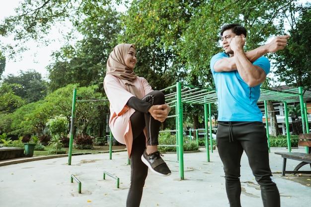 Moslimparen kletsen terwijl ze staan en doen warming-upbewegingen voordat ze in het park gaan sporten