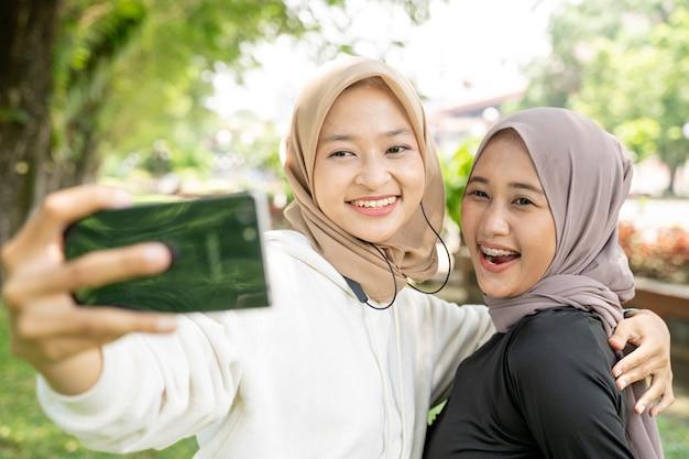 Moslimvriend die tijdens het sporten selfie of videogesprekken neemt met haar smartphone her