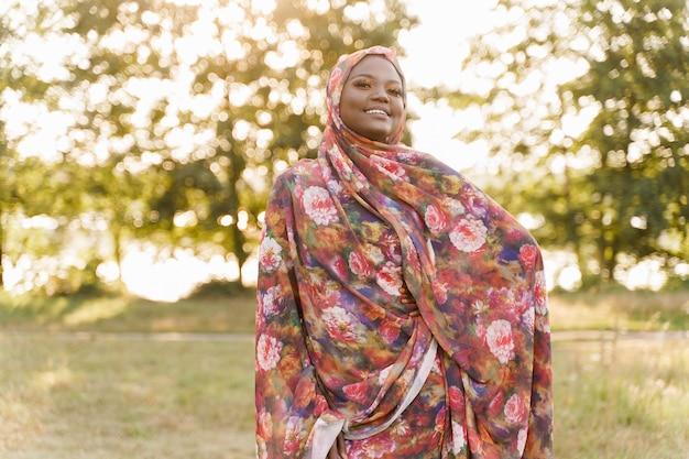 Moslimvrouw afrikaanse etniciteit weared traditionele kleurrijke hijab glimlacht op de groene weide