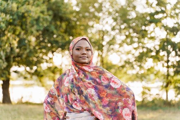 Moslimvrouw afrikaanse etniciteit weared traditionele kleurrijke hijab op de groene weide