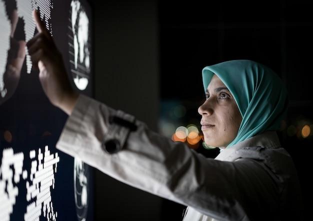Moslimvrouw bezig met slimme infographic scherm