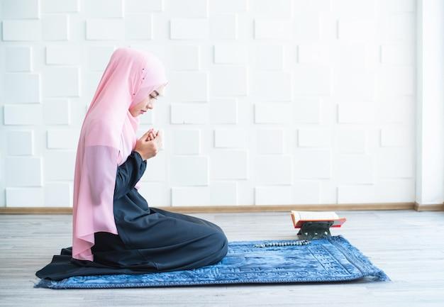 Moslimvrouw bidden op hijab binnenshuis bidden op mat