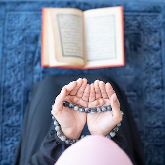 Moslimvrouw bidt met kralen en leest koran
