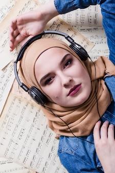Moslimvrouw die aan muziek op hoofdtelefoons luistert