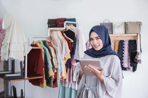 Moslimvrouw die digitale tablet in kledingsopslag gebruiken