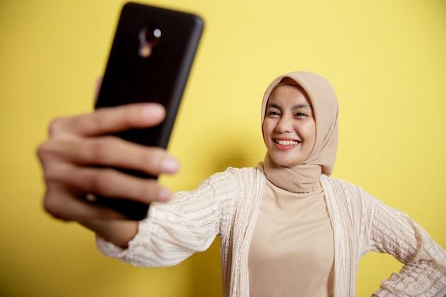 Moslimvrouw die hijab draagt die een selfie met telefoon neemt die op gele muur wordt geïsoleerd