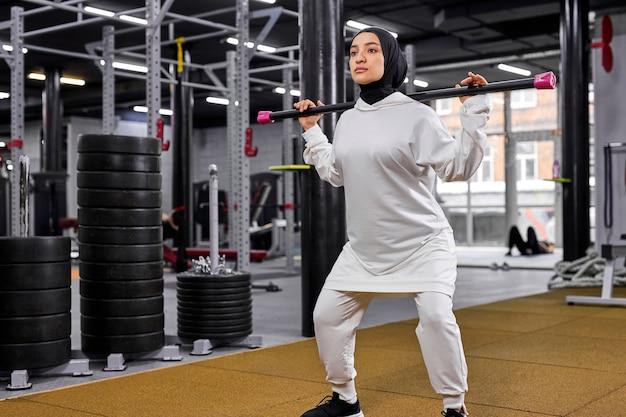 Moslimvrouw die hijab draagt, doet squats met krachttraining om in de toekomst fit, atletisch en gezond te zijn. jonge vrouw is geconcentreerd op fitness