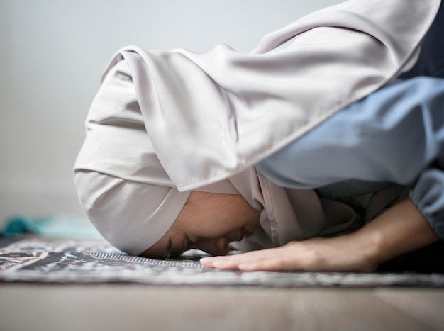 Moslimvrouw die in sujud-houding bidden