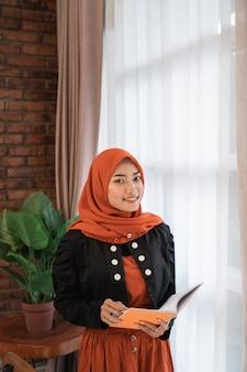 Moslimvrouw die met hoofdsjaal een boek leest