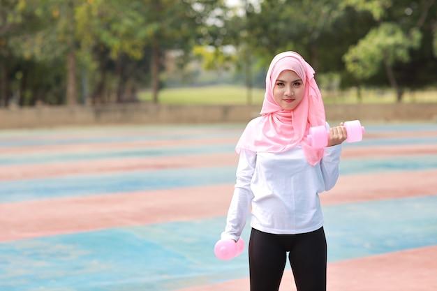 Moslimvrouw die oefeningen buiten doet