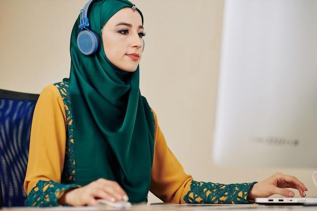Moslimvrouw die op computer werkt