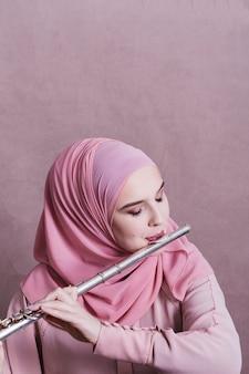 Moslimvrouw die op de fluit speelt