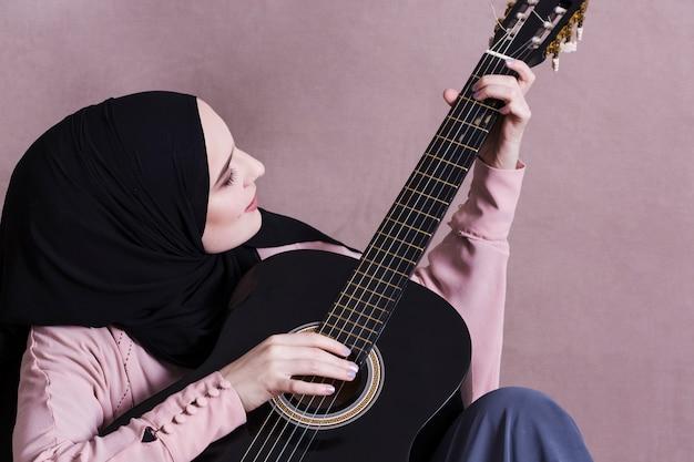 Moslimvrouw die op de gitaar speelt