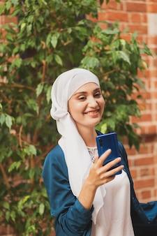 Moslimvrouw die selfie neemt, gelukkig mooi meisje met sjaal neemt een foto van haar zelf met smartphone