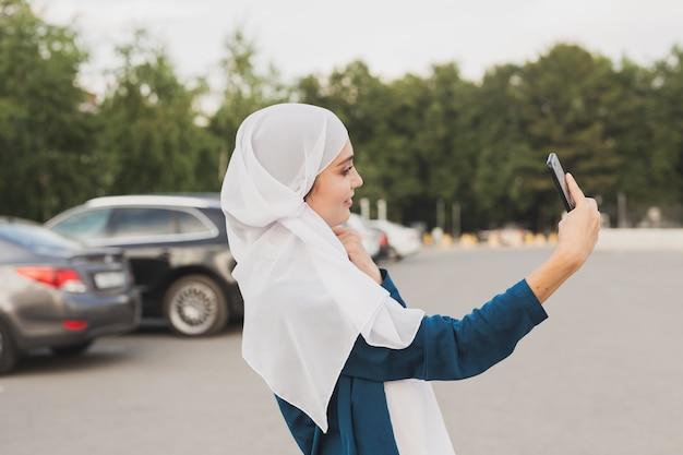 Moslimvrouw die selfie neemt. gelukkig mooi meisje met sjaal nemen foto van haar zelf met behulp van smartphone.