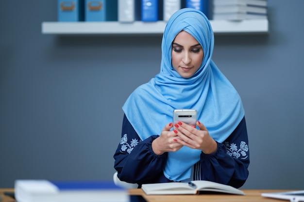 Moslimvrouw die smartphone op kantoor gebruikt
