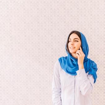Moslimvrouw die telefoongesprek maakt