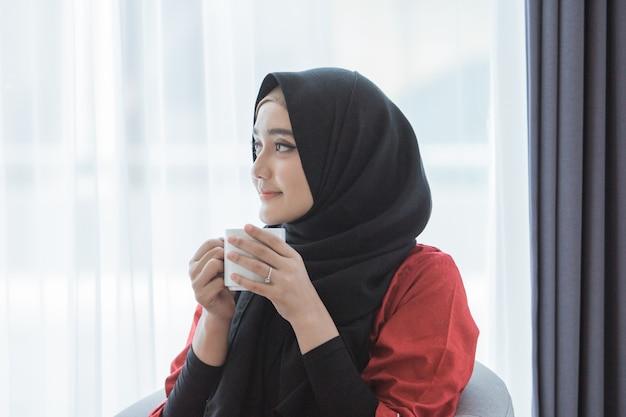Moslimvrouw die van koffie thuis genieten