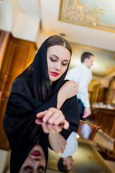 Moslimvrouw die zwarte hijab wering