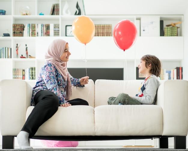 Moslimvrouw en kleine jongen spelen met ballonnen thuis