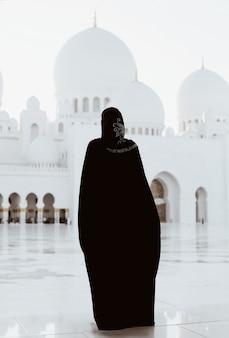 Moslimvrouw in abaya bij witte minaret