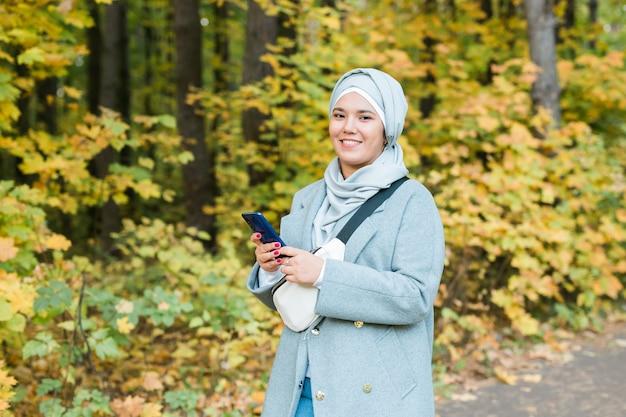Moslimvrouw in het park met behulp van smartphone online draadloos verbonden