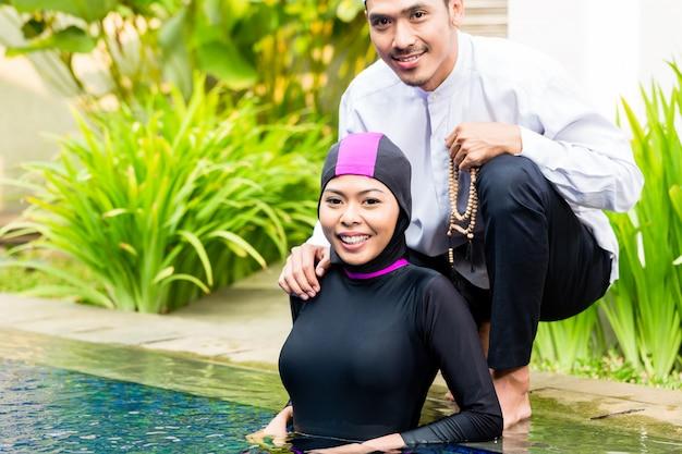 Moslimvrouw in pool die haar echtgenoot begroet