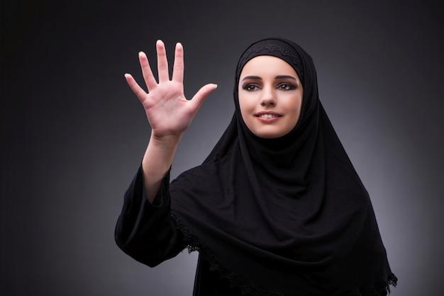 Moslimvrouw in zwarte kleding tegen donkere achtergrond