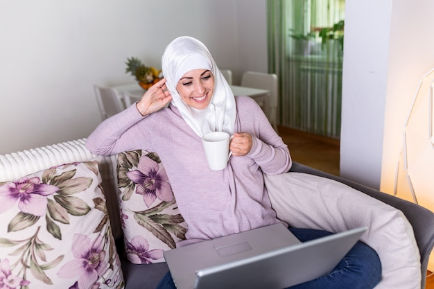 Moslimvrouw met behulp van haar laptop, thuis surfen op sociale netwerken