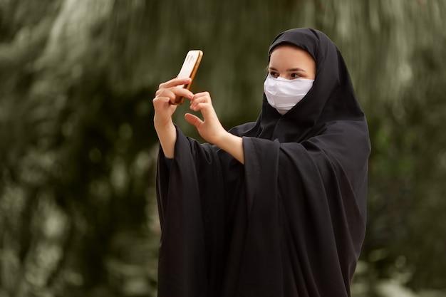 Moslimvrouw met chirurgisch masker die een selfie maakt met haar smartphone covid19 coronavirus