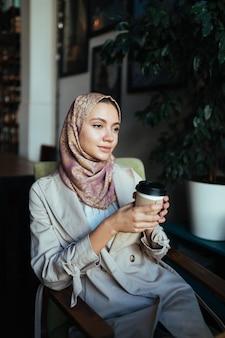 Moslimvrouw met een doordachte blik zit in een café en houdt koffie in haar hand
