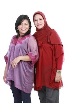 Moslimvrouw met haar dochter die over witte backround wordt geïsoleerd