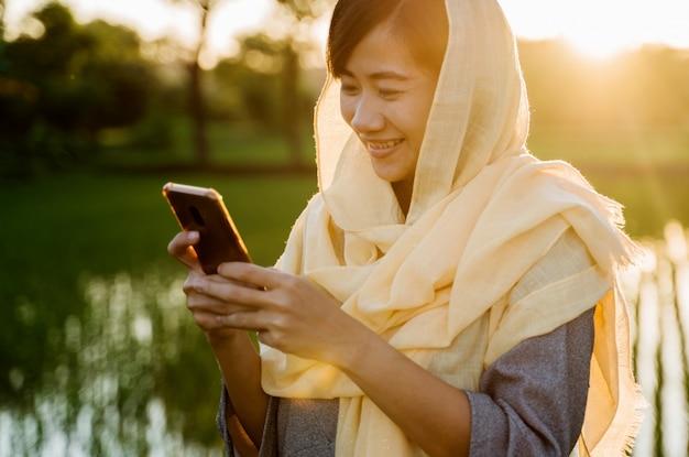 Moslimvrouw met hijab met behulp van mobiele telefoon