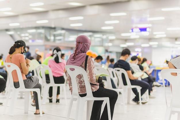 Moslimvrouw met hijab wacht in de rij om vaccin tegen coronavirus te ontvangen