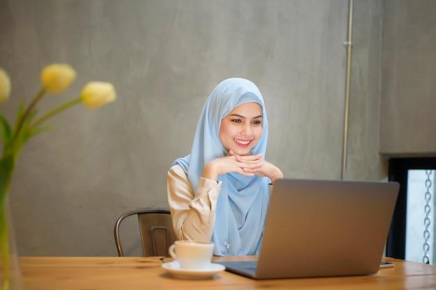 Moslimvrouw met hijab werkt met laptopcomputer in coffeeshop