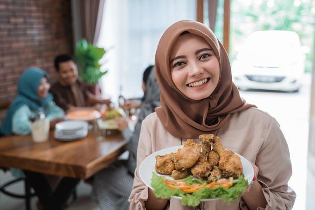 Moslimvrouw met voedsel geserveerd voor familie