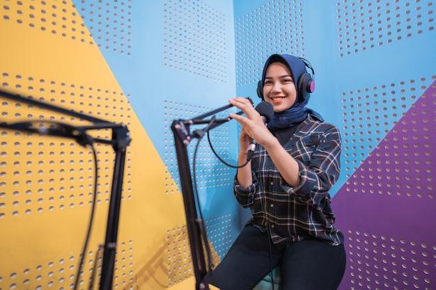 Moslimvrouw neemt een podcast op in haar studio