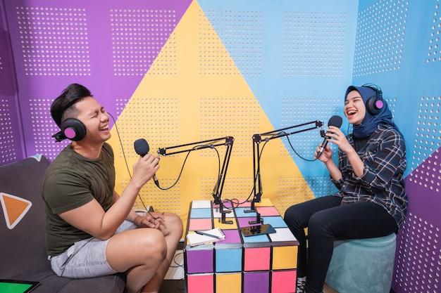 Moslimvrouw neemt podcast op met een man in de studio