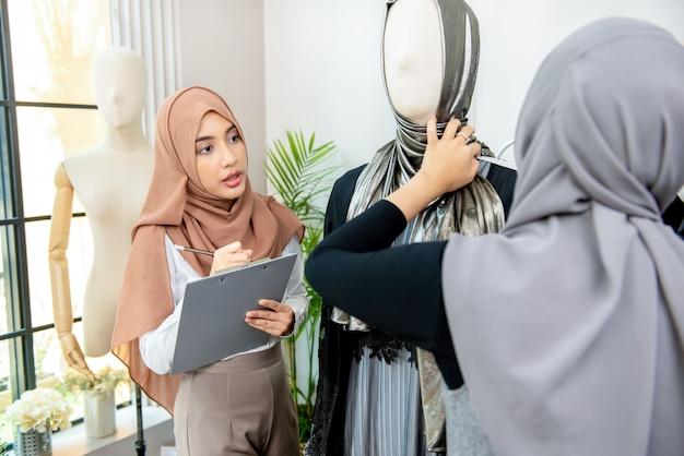Moslimvrouw ontwerper die met collega werkt die grootte van de kleding meet