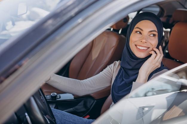 Moslimvrouw praten aan de telefoon in haar auto