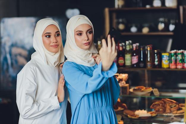 Moslimvrouw praten op mobiele telefoon in een café