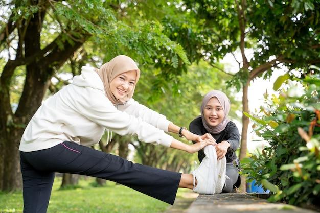 Moslimvrouw vriend atleet haar been buiten samen uitrekken