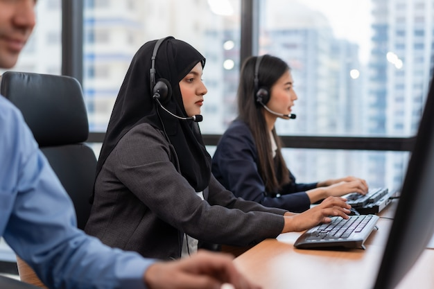 Moslimvrouw werkt in een callcenterexploitant en klantenservicemedewerker met microfoonkoptelefoons aan een computer in een callcenter