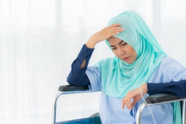 Moslimvrouw zittend in een rolstoel.