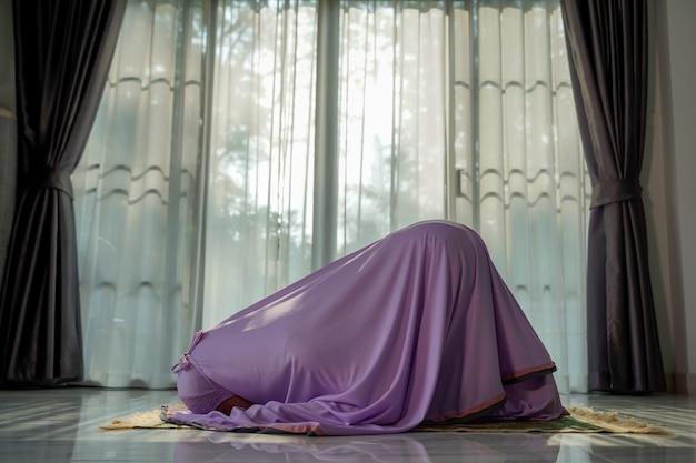 Moslimvrouwen bidden in de foyer van het huis tijdens de uitbraak van het coronavirus (covid-19), quarantaineconcept.