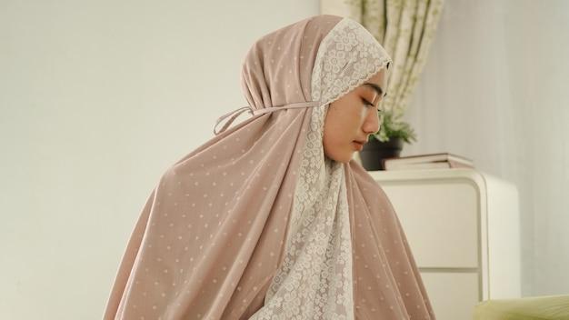 Moslimvrouwen bidden met begroetingsgebaren en dragen een mukenah