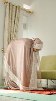 Moslimvrouwen bidden met een buigende beweging terwijl ze een mukenah dragen