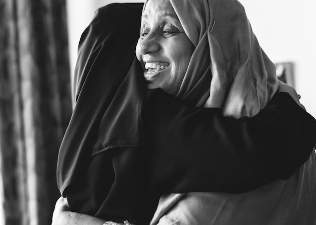 Moslimvrouwen die elkaar knuffelen