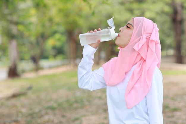 Moslimvrouwen drinkwater buiten