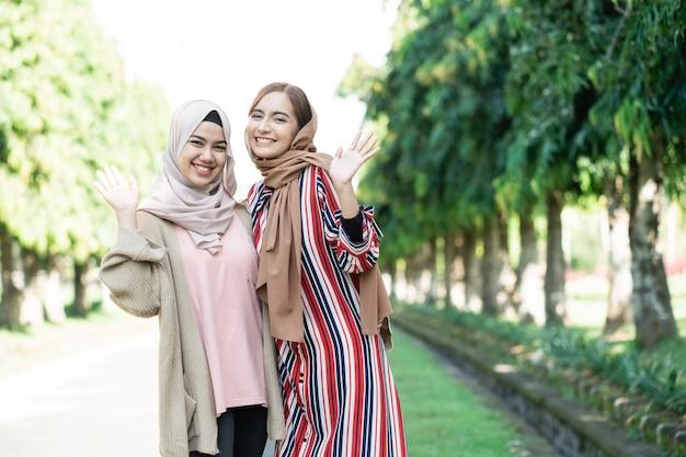 Moslimvrouwen in hijabs buitenshuis op zonnige dag met een gelukkige vriend zwaaien met hun hand naar de camera